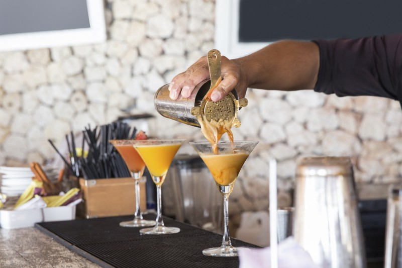 Male bartender pouring coffee martini