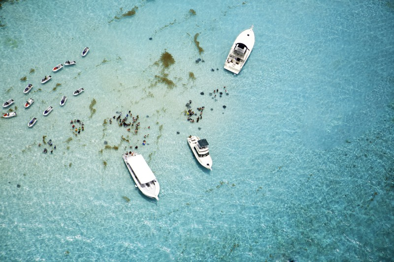 Aerial view of boats and stingrays in water at Stingray City on Grand Cayman, Cayman Islands. It is a shallow area where visitors can swim with and touch the stingrays in the water. It's a beautiful tropical day for this popular attraction. Taken with a Canon 5D Mark 3. rm